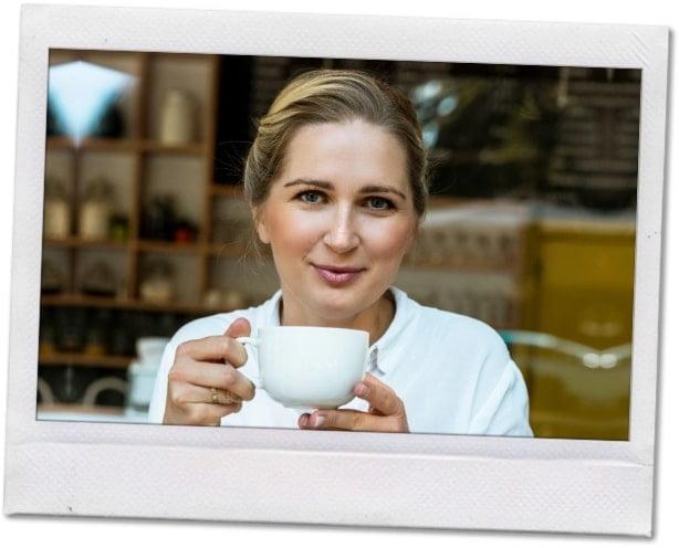 Uśmiechnięta kobieta zfiliżanką kawy.