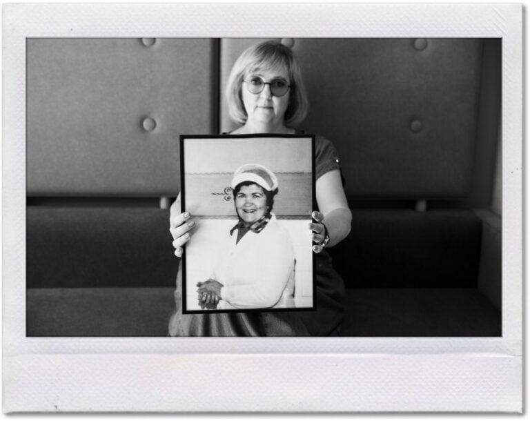 Czarno-biała fotografia wnuczki ze zdjęciem swojej babci.
